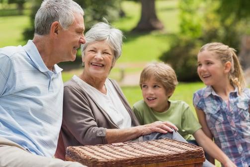 Portrait of a smiling senior couple and grandchildren at the park