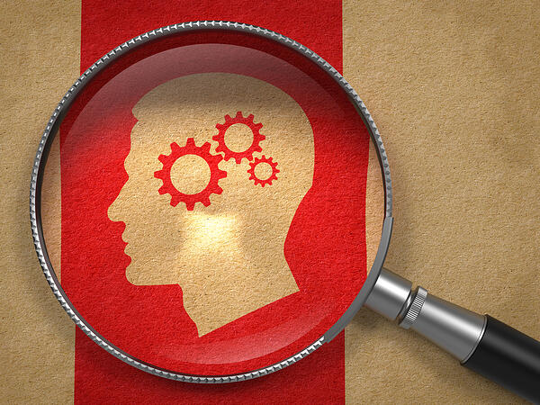 Magnifying Glass with Icon of Profile of Head with Cogwheel Gear Mechanism on Old Paper with Red Vertical Line Background.