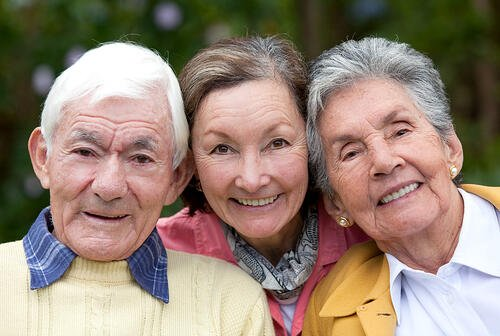 Old couple and their daughter smiling outdoors