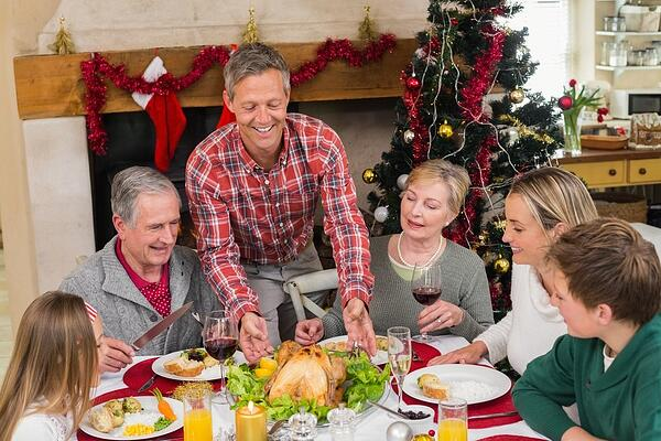 Man serving roast turkey at christmas at home in the living room